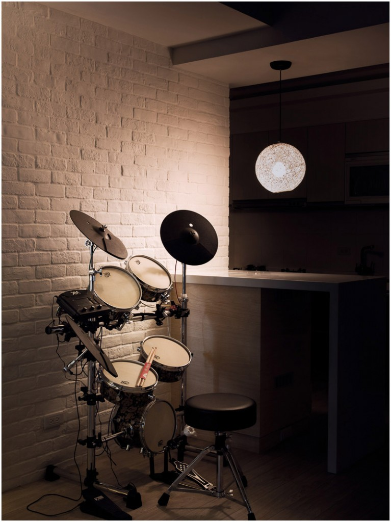 On one side of the small galley kitchen is another music nook, this time containing a drum set. A small circular pendant light hangs above the kitchen bar.