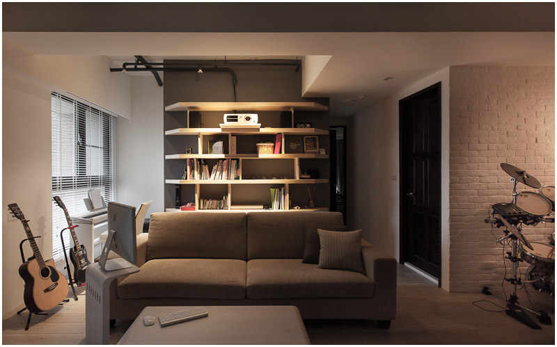 This view of the living room from the far wall, showing the living room. The wall behind the couch has light wood shelving that contrasts beautifully with the black paint. A projector is  on the top shelf. A small nook to the left holds a keyboard and two guitars, acting as a small music nook. The hallway to the right leads to the bathroom and bedroom.