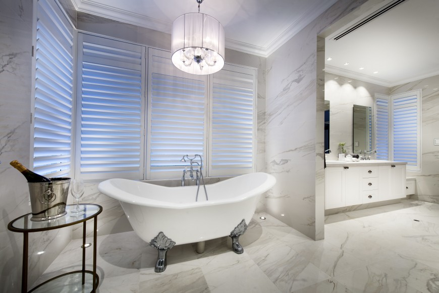 Shutters may be opened while bathing to take advantage of the view, or stay closed for privacy. A wine bucket rests nearby. Two floor lights on either side of the claw-foot tub ensure that there isn't an absence of light.