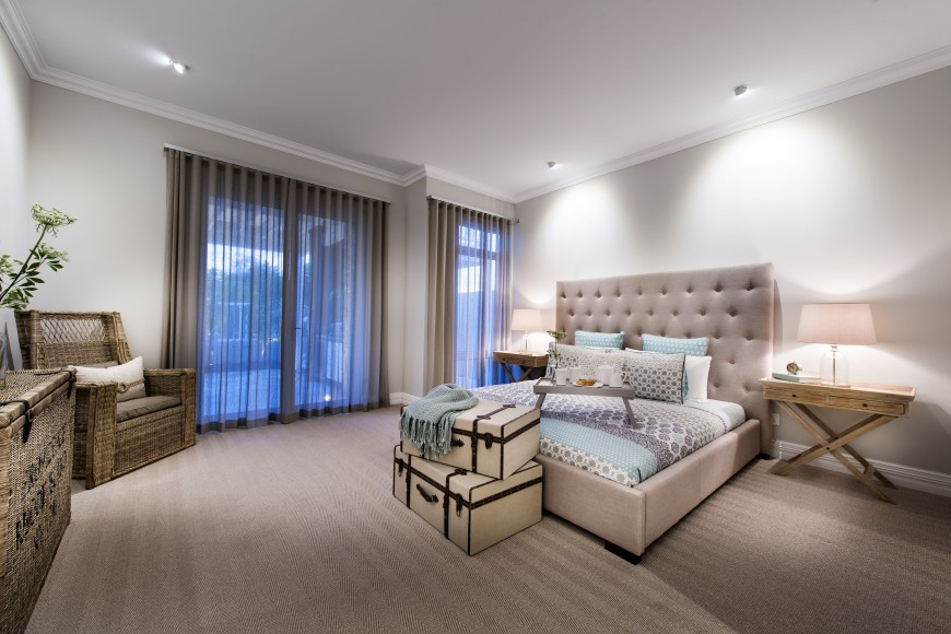 The wicker furniture and luggage accents make another appearance in the guest bedroom. The pastel patterned bedding is tucked into a beige plush platform bed. The low carpet has a subtle striped pattern.