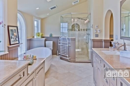 The recently renovated master bathroom includes a spacious shower enclosure with a towel rack on the side, a large soaking tub in front of one of the windows, archways and several vanities.
