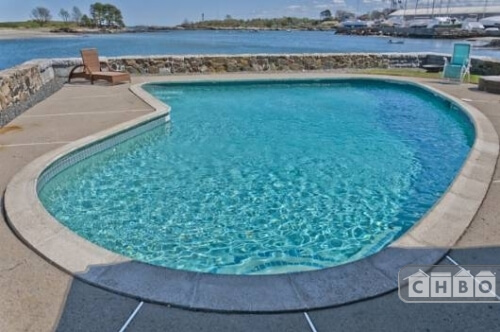 The swimming pool has concrete all around it and is separated from the ocean by a stone wall.