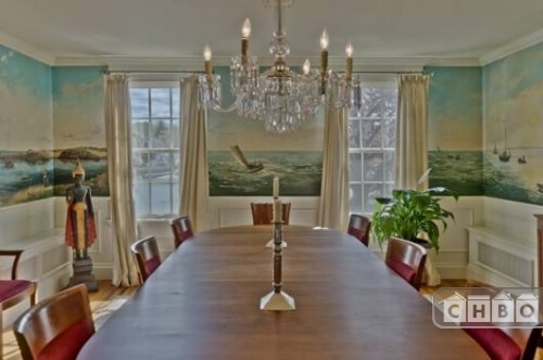 The formal dining room has an immense antique hardwood table with red upholstered seats, white crown molding, wainscoting and an elegant crystal chandelier. The walls are painted with scenes of the sea, which can be seen through the windows of the room.