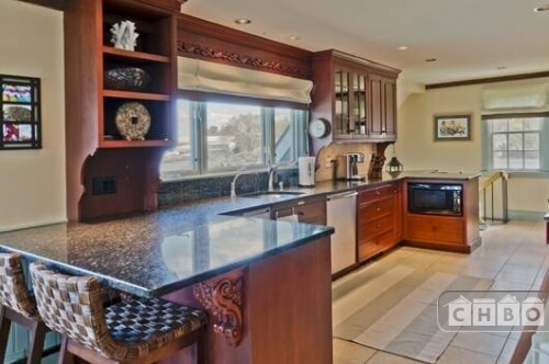 The spacious kitchen has high-end appliances built into the counter and beautiful details on the small eat-in bar and along the top of the window. The light tile floor is easy to keep clean.