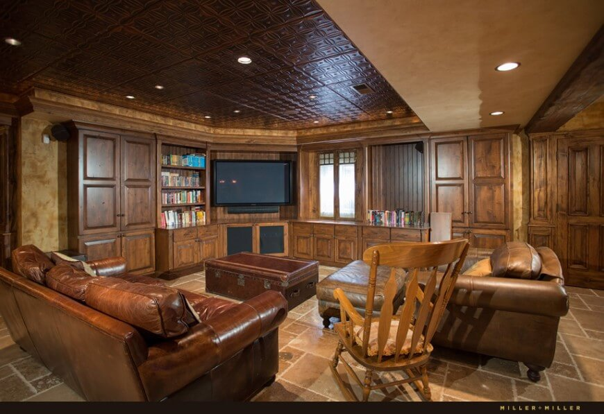 The adjoining room is a home theatre with leather sofa and armchair. An old suitcase acts as a coffee table. The room also has built in bookcases.