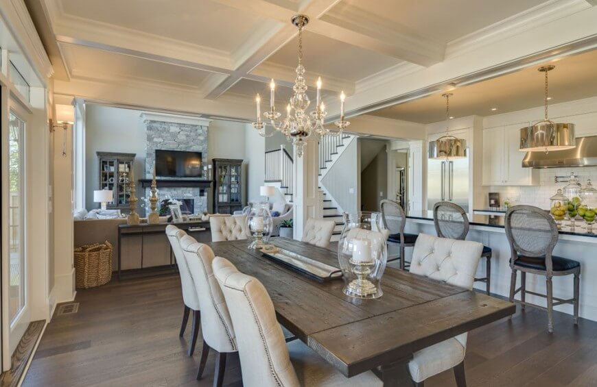 The kitchen opens up into the dining room, which features a large plank table and cushy seating for eight. A coffered ceiling differentiates the rooms.