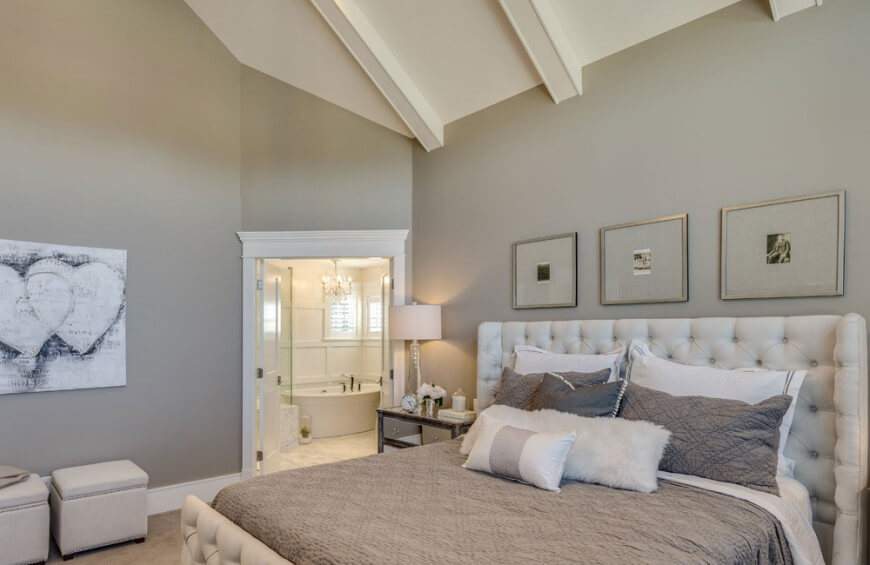 The upstairs master bedroom has an on-suite bathroom and a cool, neutral color palette. A trio of old photographs top the plush quilted bed frame.