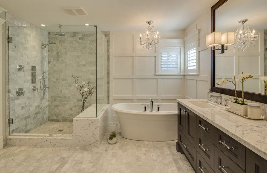 The master bathroom has a large stone and tile glass-enclosed shower stall, complete with a bench. A small chandelier hangs above the large soaking tub. The dark-wood vanity is topped with marble.