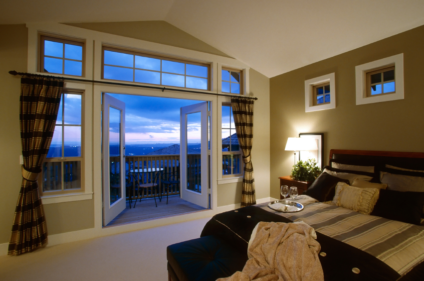 This contemporary striped bedroom has glass doors that open out to a balcony with a view.