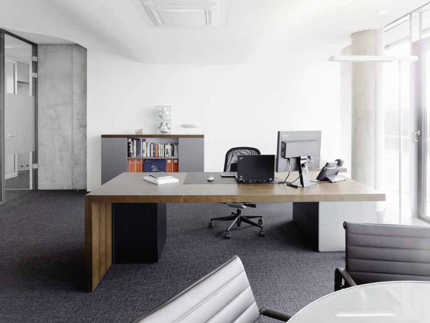 Finally, we leave you with one of the singular offices, housing a minimalist natural wood desk over grey carpeting, with the undulating ceiling above and full height exterior glass to the right.