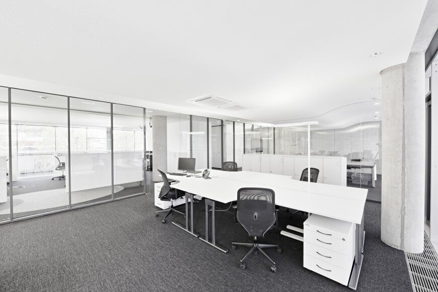 Glancing down the row of office spaces separated by floor to ceiling glass, one can appreciate the open nature of this design, lending the discrete spaces a sense of continuity. Sleek white and metal desks emphasize the brightness.