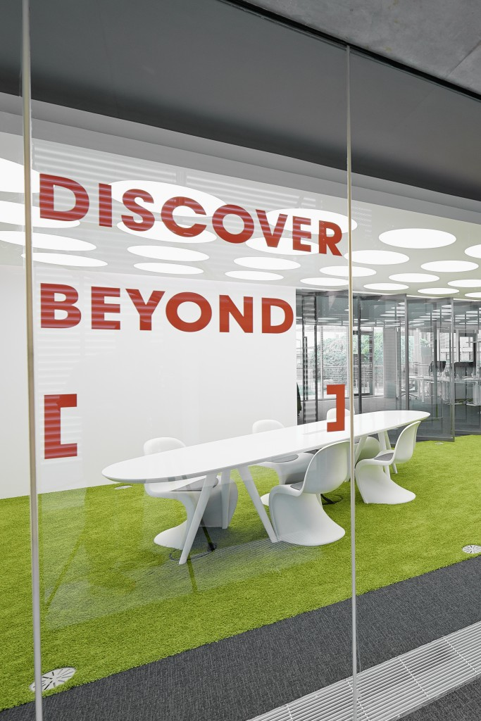 One of many discrete conference zones, this astroturf-like space contrasts the bright green floor hue with white and grey surroundings.