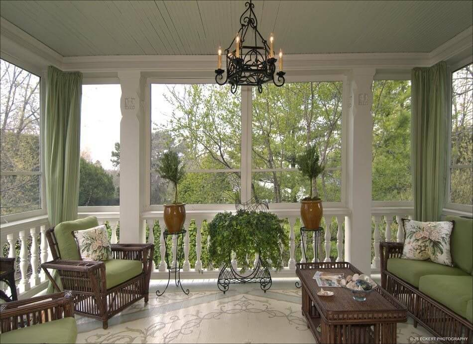 a gorgeous screened porch with beautiful flooring and elegant furniture in dark wicker and pale green