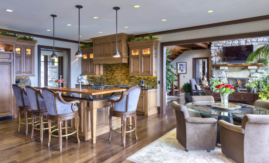 The open design kitchen centers on a large natural wood island with full dining space on an elevated platform. Cabinets feature lighting inside and below, and cozy dining area centered on a glass top table stands at right.
