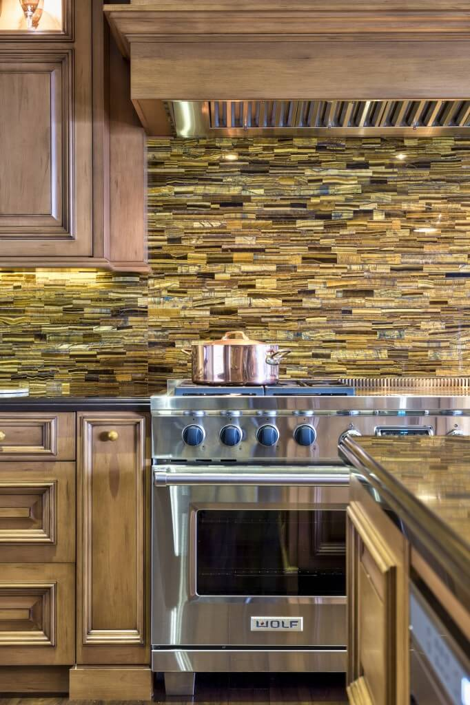 The kitchen features an intricate tile backsplash sandwiched between layers of rich wood cabinetry. Stainless steel appliances add a modern touch to the rustic style.