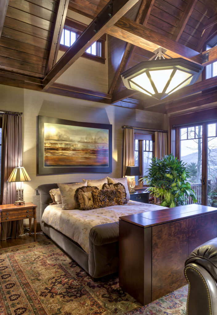 Master bedroom plays host to a mountain of detail, from the ornate area rug to the hidden television cabinet, all standing below an elaborate chandelier and exposed beam vaulted ceiling. The retractible glass and wood panels appear here as well, helping blend the interior and outdoors.