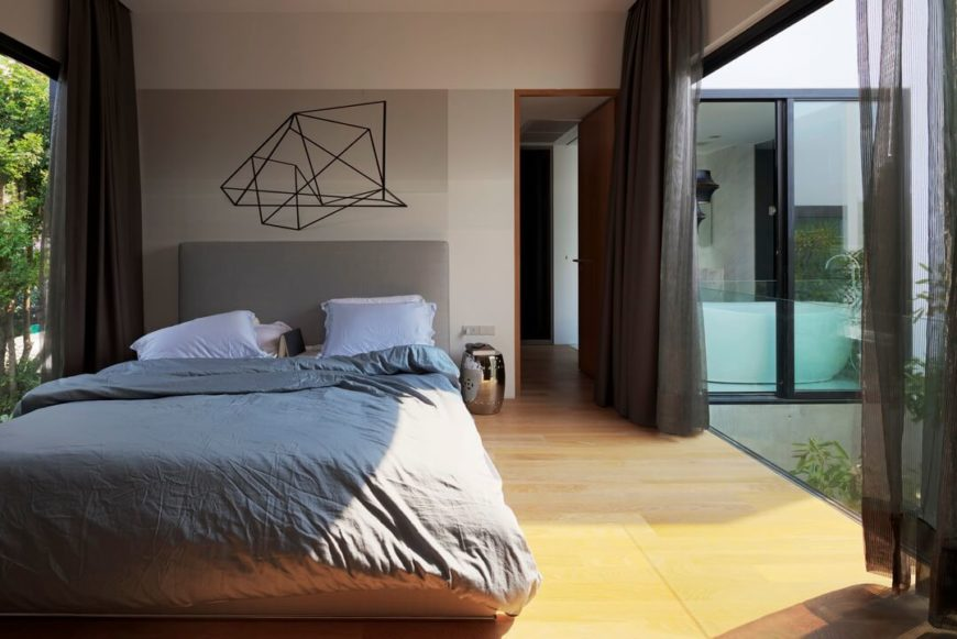 Master bedroom, located in the upper level box structure, features rich hardwood flooring in contrast to the dark and modern sleek surfaces found elsewhere. Full height glass on both sides opens the space to the environment.