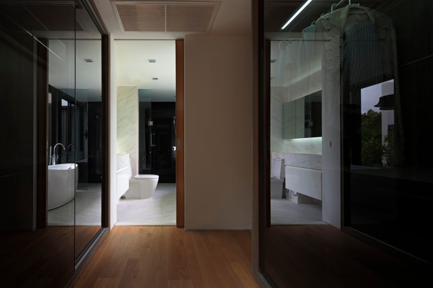 Peering through the large walk-in closet, featuring glass-panel storage, we see the master bath, decked out in white marble.