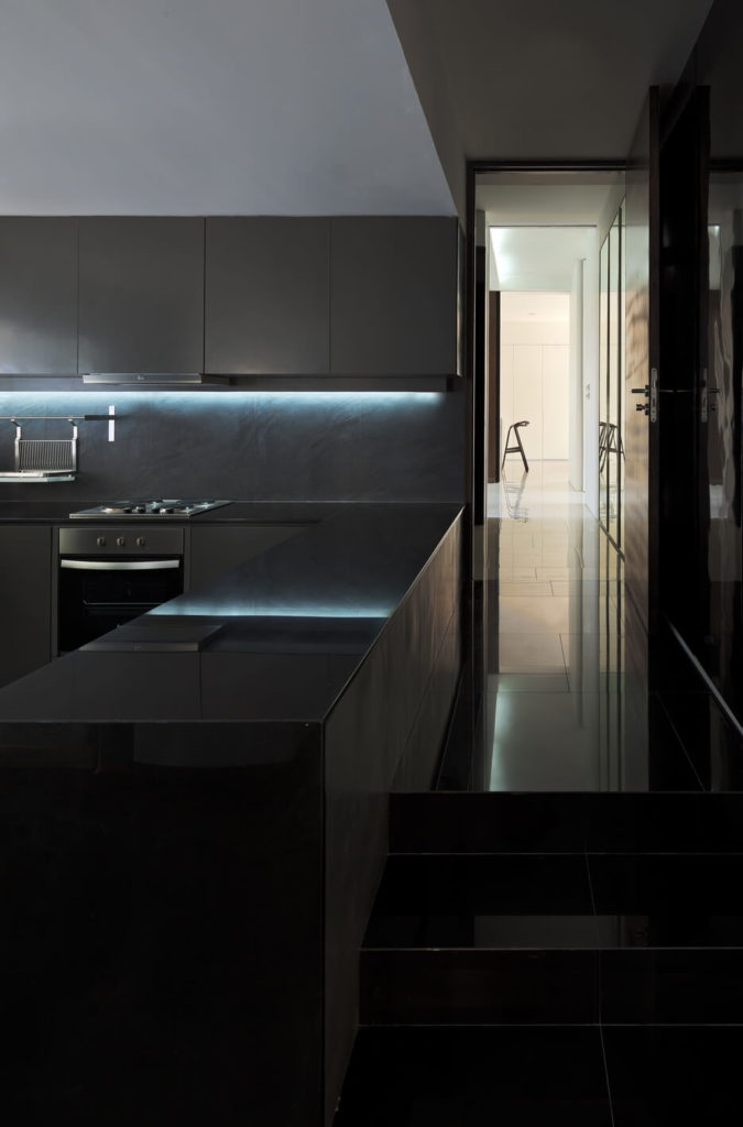 Turning a corner from the kitchen, we see down a lengthy tile-floored hallway. Metallic countertops and subtle under-cupboard lighting highlight the modern style of the home.