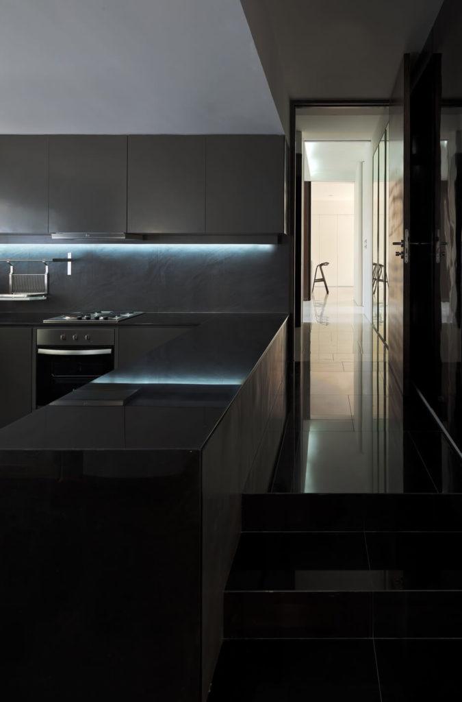 Повернув за угол из кухни, мы видим длинный кафельный пол прихожей. Металлические столешницы и тонкий под шкаф освещение подчеркивают современный стиль дома.
