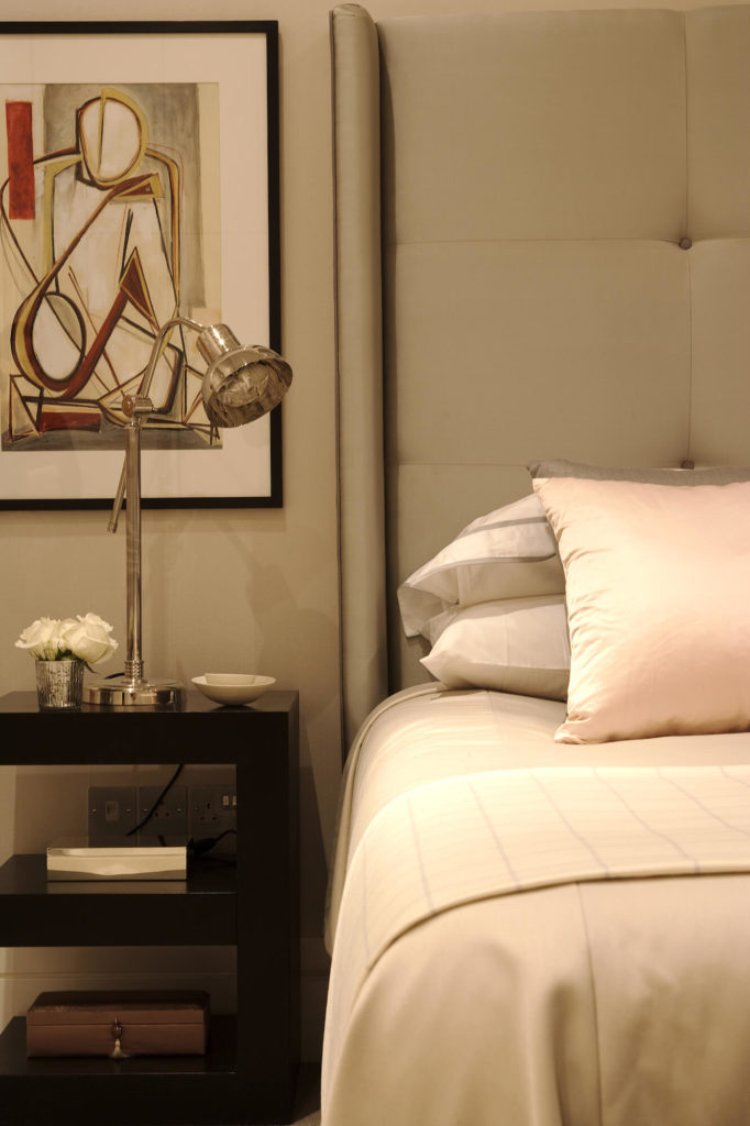 With a closer look, we see the interplay between the chromed bedside lamp, jet-black table, and cream surroundings.