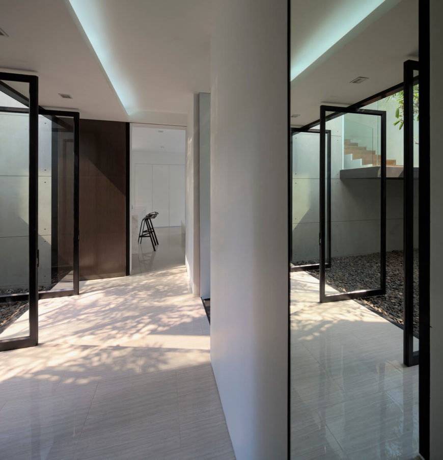 Returning to the lower level, we see the glass hallway panels in fully open position, allowing for cross ventilation throughout the home.