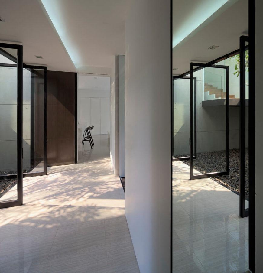 Возвращаясь на нижний уровень, мы видим стеклянный прихожей панелями в полностью открытом положении, обеспечивая сквозную вентиляцию по всему дому.