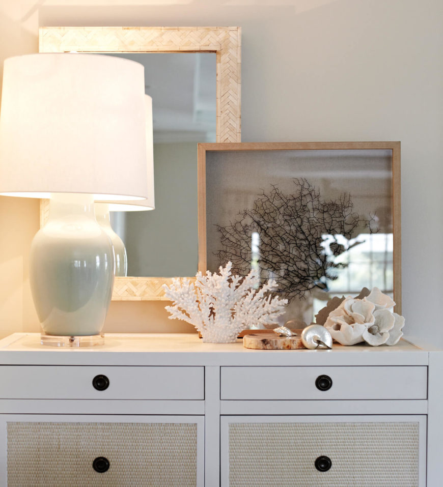 A close up of one of the white dressers at the rear of the living room shows the beach accents and muted blue lamp. Behind the dresser is a mirror on the wall, overlapped by a metallic piece of art leaning against the wall.