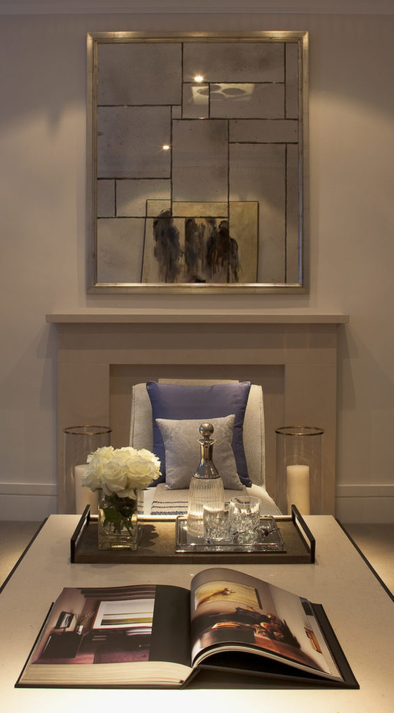 Set in a different configuration, we see a white topped table here before the marble fireplace. The fragmented mirror above adds a modern rustic aspect to the room.