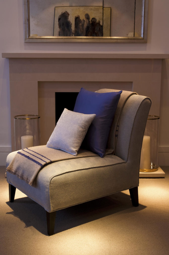 A singular armless accent chair with detailed patterns stands before the fireplace, flanked by a pair of cylindrical candle holders.