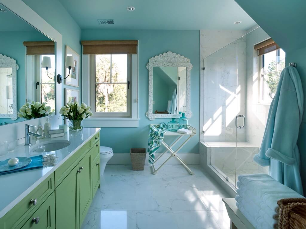 the bright blue of the walls is complemented by a lovely green vanity topped with white