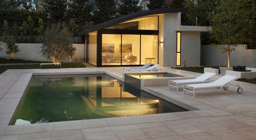 this simply designed square pool has an adjoining hot tub on a higher level than the