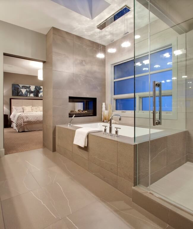 This ultra-modern en suite holds a grey tile covered bathroom in which a glass shower enclosure, large window side soaking tub, and pass-through fireplace line neatly against the exterior wall.