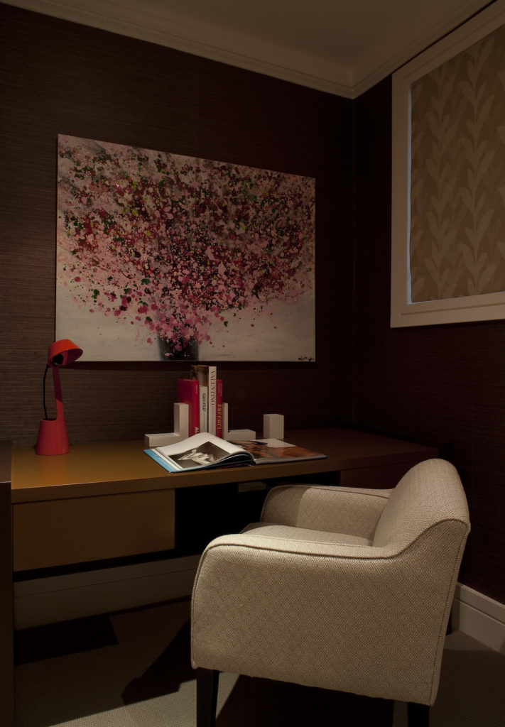 The study holds this contemporary brown writing desk  and plush accent chair below another distinctly striking painting. The high contrast between bold art pieces and neutral hued furniture unifies the interior.