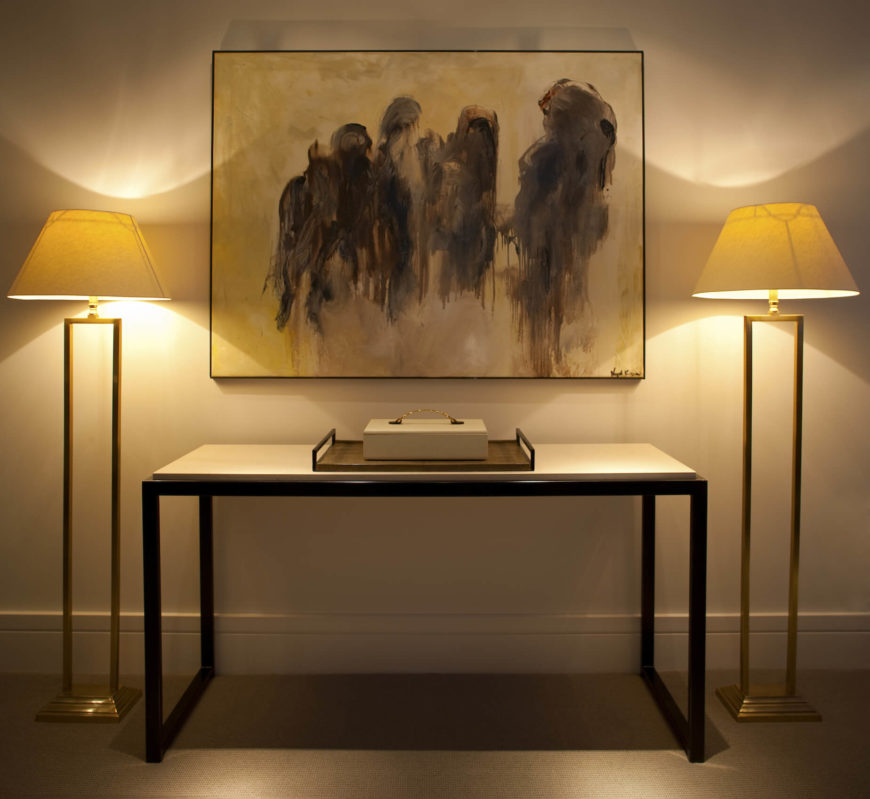 At the opposite end of the room, we have a minimalist, black frame and white topped side table, standing beneath another bold painting. A pair of similarly minimalist gold hued floor lamps flank the setting.