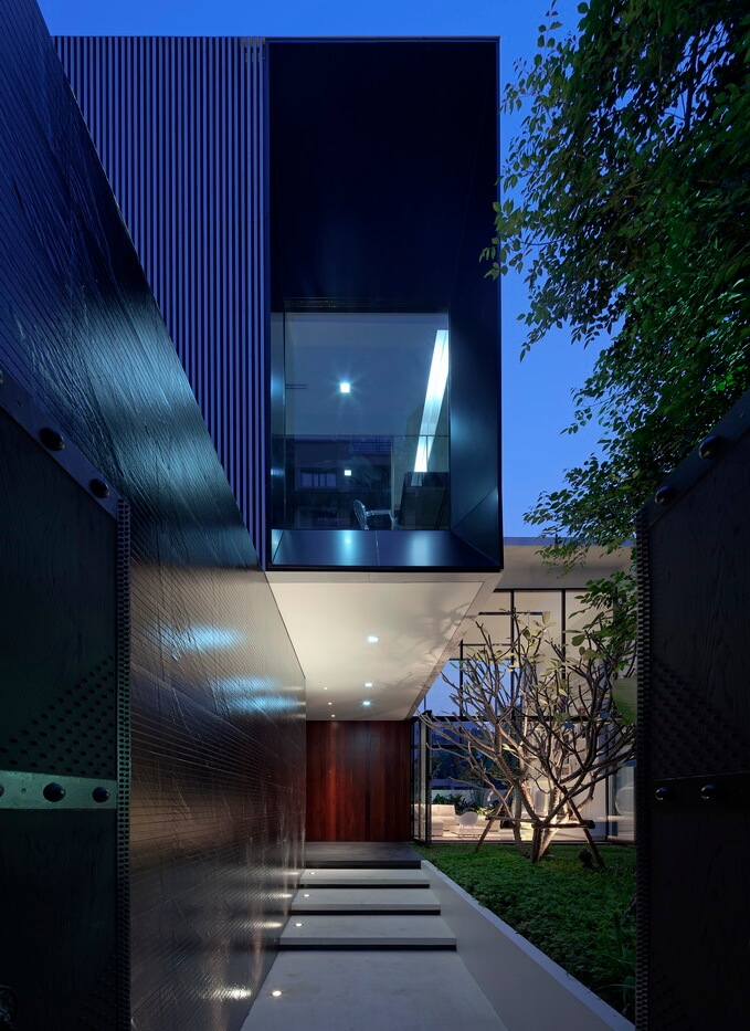 Walking up the main entryway, the dark walls give way to the metallic box structure above. Rich wood paneling surrounds the entrance at center.