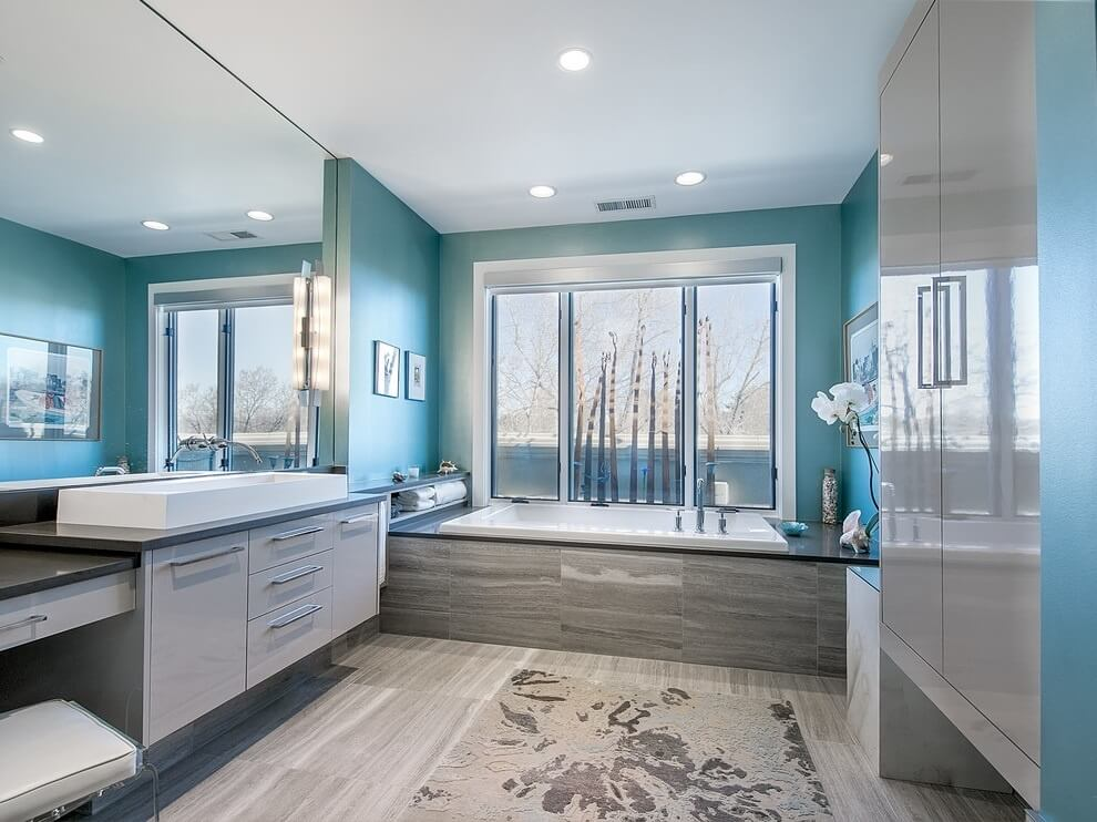 this modern bathroom has smooth lined cabinetry and appliances the bold blue walls contrasts gorgeously