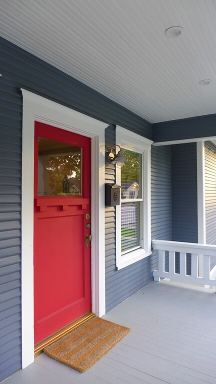 The Blue Siding Of This Home Contrasts Beautifully With The Red Door. The  Small White