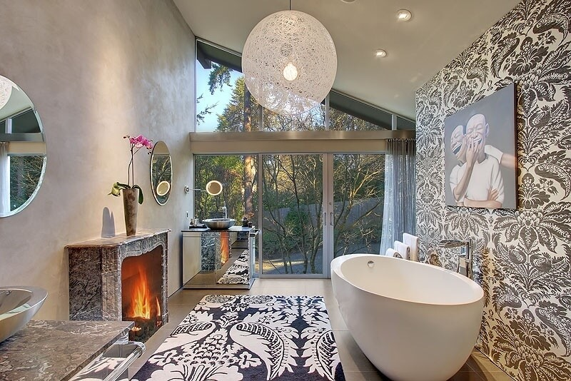 This high ceiling bathroom splashes an array of detailed texture, with floral print wall and area rug paired against beige tile flooring. Full height exterior glass leads to a patio, while large pedestal tub stands across from marble wrapped fireplace.