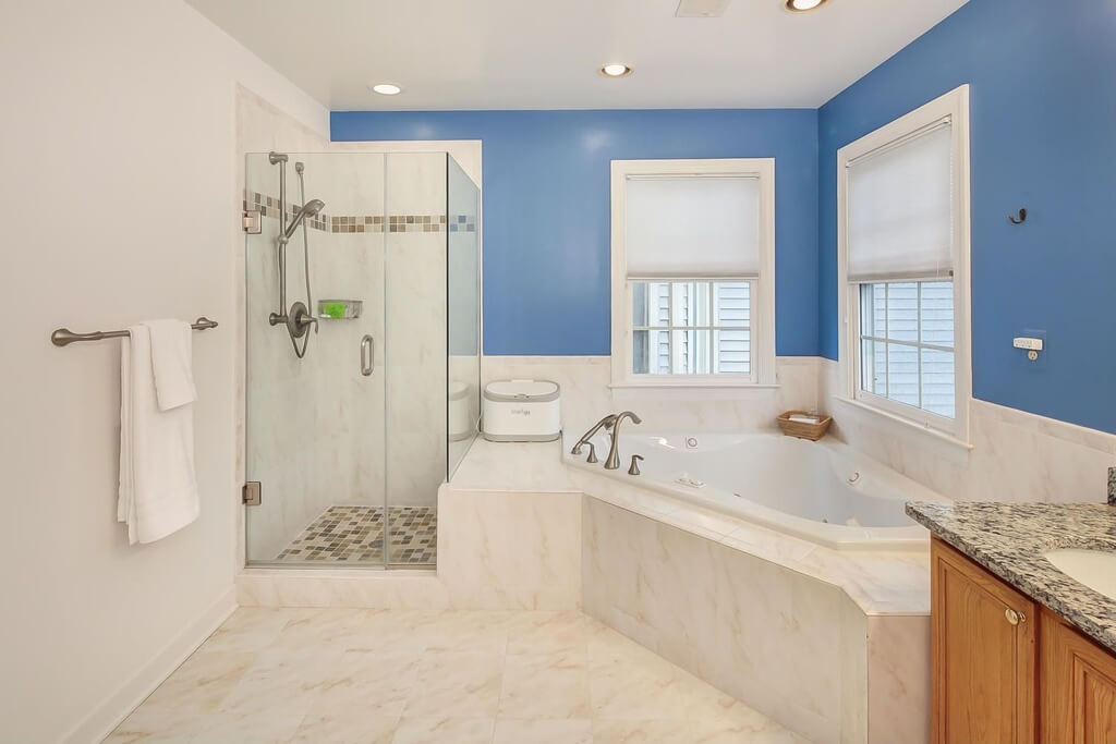 The light cream marble tile extends into the bathtub enclosure  with  brushed nickel fixtures. 27 Cool Blue Master Bathroom Designs and Ideas  Pictures