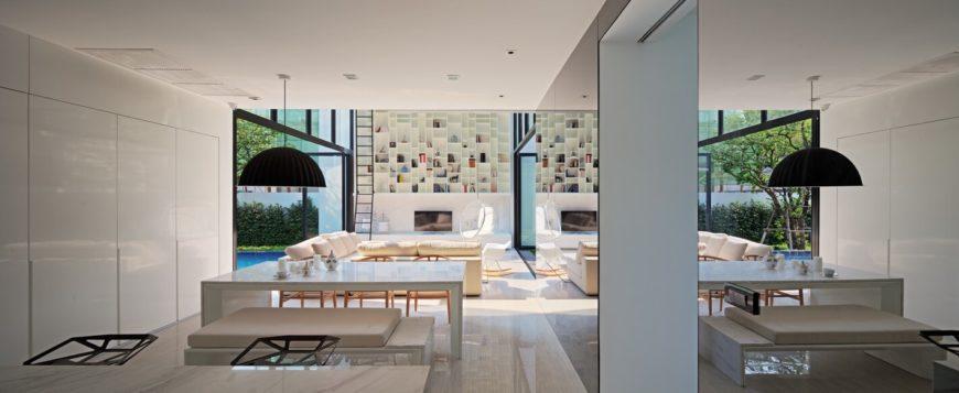 Большой открытый дизайн гостиной дома огромный, двухэтажный книжной полке у дальней стены, окруженная bespoke белые современной мебелью.