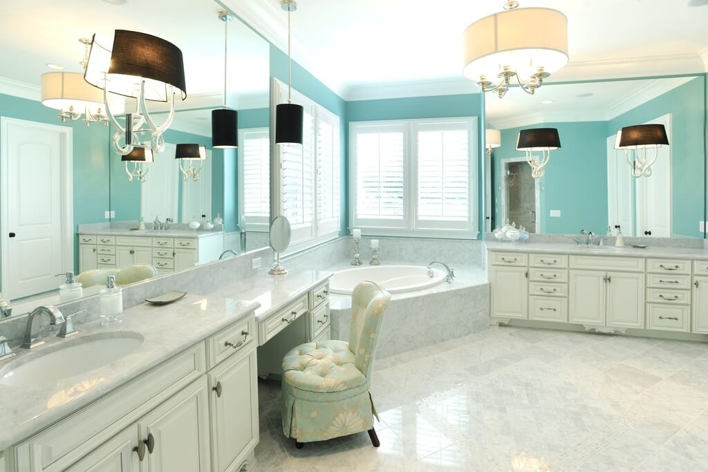 This spacious  luxurious bathroom has two separate vanities with a  marble enclosed bathtub between. 27 Cool Blue Master Bathroom Designs and Ideas  Pictures