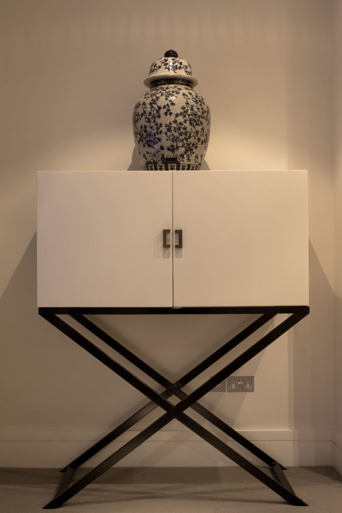 This free standing cabinet serves as a perfect example of the bespoke minimalism of this home interior, with a simple cubic shape and black and white contrast.