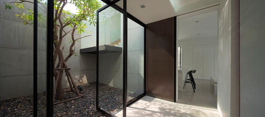 В этом пространстве на всю высоту стеклянные панели, чтобы отдохнуть в уединенном саду, со стеклом, завернутый лестница в центре.