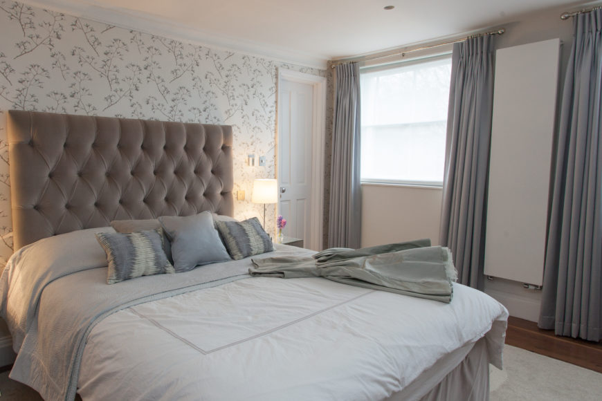 The master bedroom adds a dash of texture to the muted greys and browns of the home, with floral wallpaper and a large button tufted headboard.