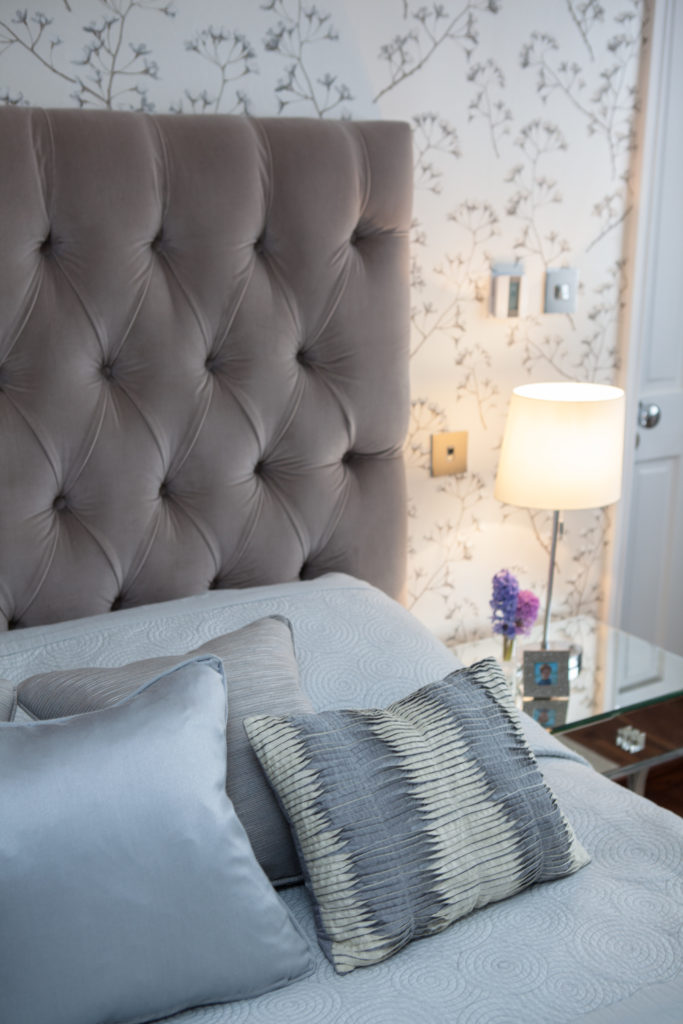 Bed coverings include sky blue tones and a textured throw pillow, next to glass topped bedside table.