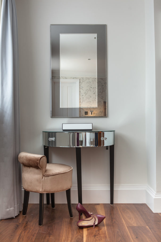 A unique circular, mirrored side table stands with a thick upholstered chair here, forming a small vanity in the bedroom.