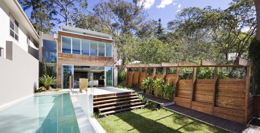 Swimming pool and small grassy area in backyard surrounded by trees. Home designed by Base Architecture