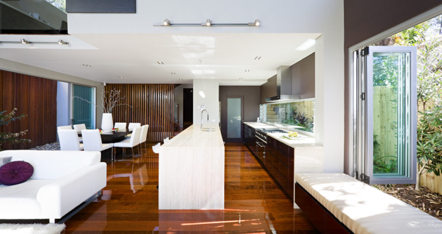 The kitchen is a lengthy space defined within the large open area by the marble topped island at center. An array of retractible window panels at right opens the space toward the outdoors.