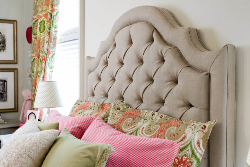 The button-tufted headboard is nice and soft, and complements the bolder paisley, pink checkered, olive, and felt bedding nicely. The paisley pillows match the fabric of the curtains.